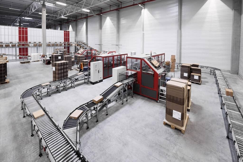 AutoStore mit Anbindung an Fördertechnik mit automatischem Kartonverschließer und Kartonaufrichtung