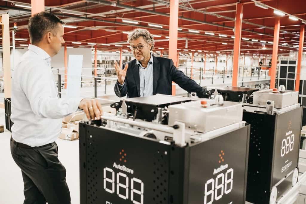 Niels Hemmingsen von Boozt diskutiert mit Havard Hallas von Element Logic an einem Black Line AutoStore Roboter