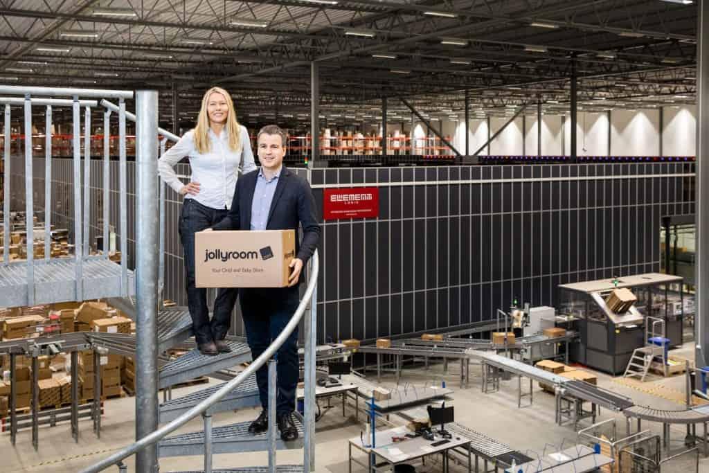 Menschen stehen lächelnd vor AutoStore-Anlage in Lager von Jollyroom