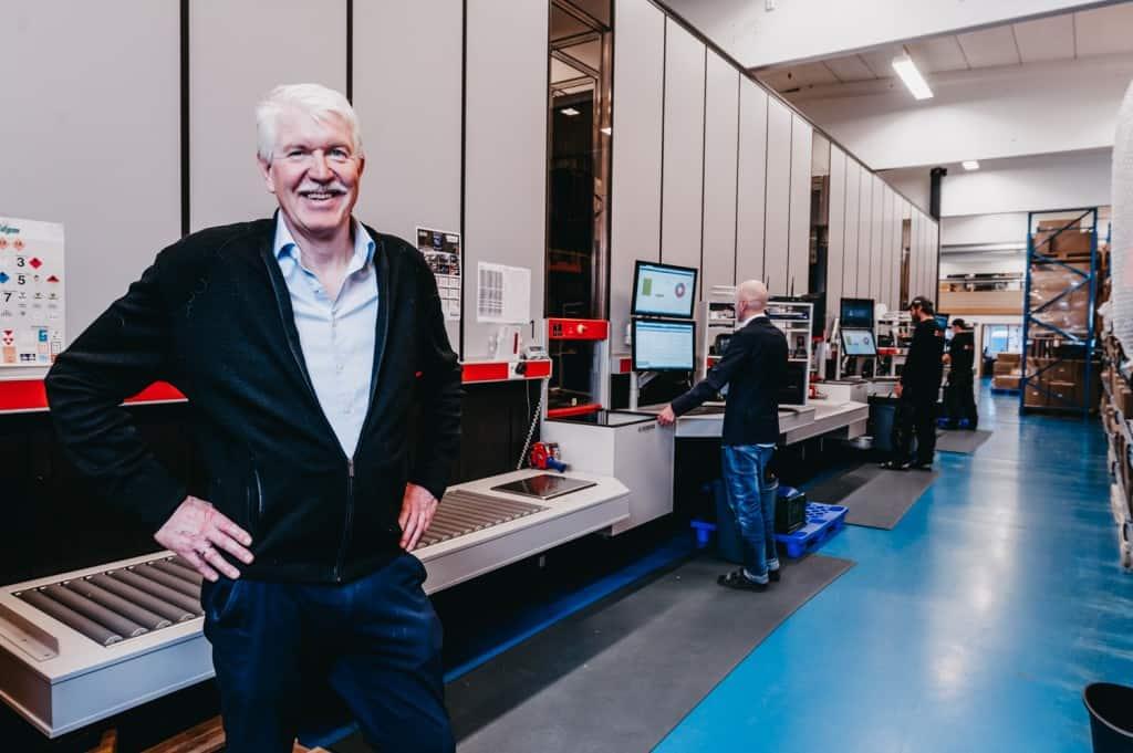 Jan Kleven, der Geschäftsführer von Elotec, steht vor der AutoStore Anlage und lächelt stolz in die Kamera, während die Mitarbeiter im Hintergrund die Ports bedienen.