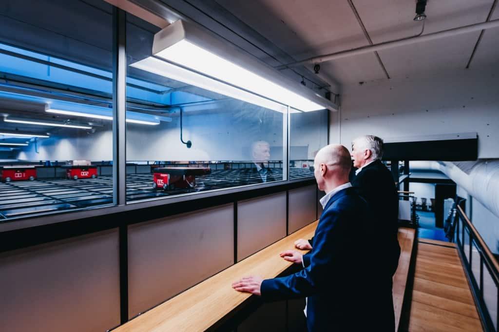 Jan Kleven and Roger Furnes beobachten, wie sich die AutoStore Roboter über das Grid bewegen.
