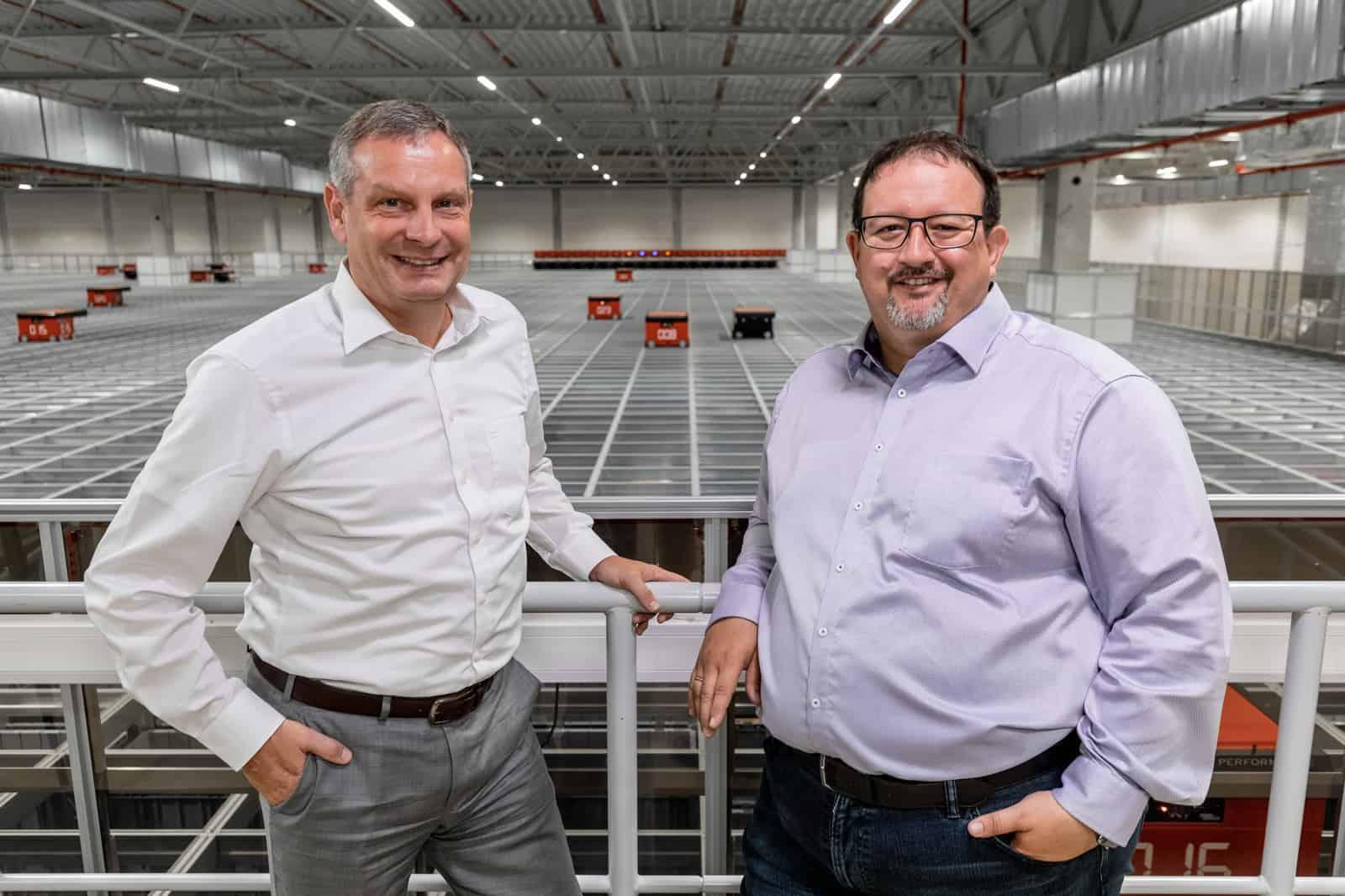 Thomas Rolle und Michael Kawalier stehen vor der AutoStore Anlage bei TTI